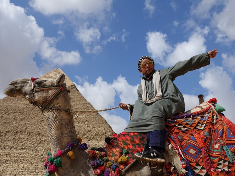 Egyptian man with camel at pyramid in Giza